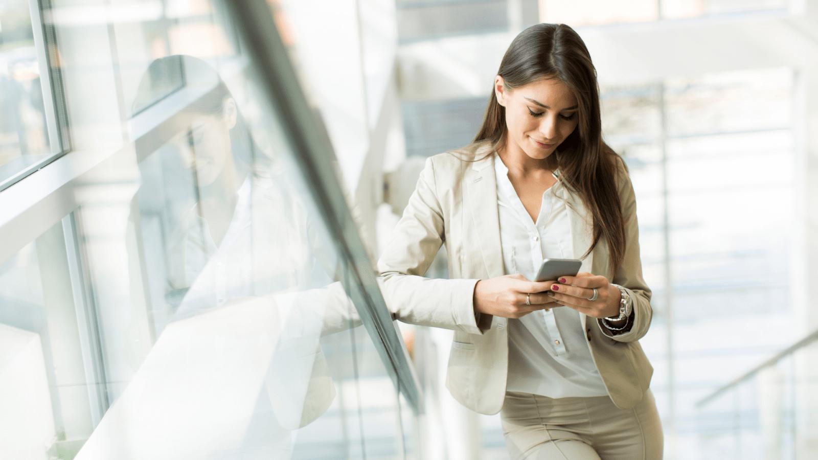 Kobieta stojąca na schodach patrząca w ekran telefonu